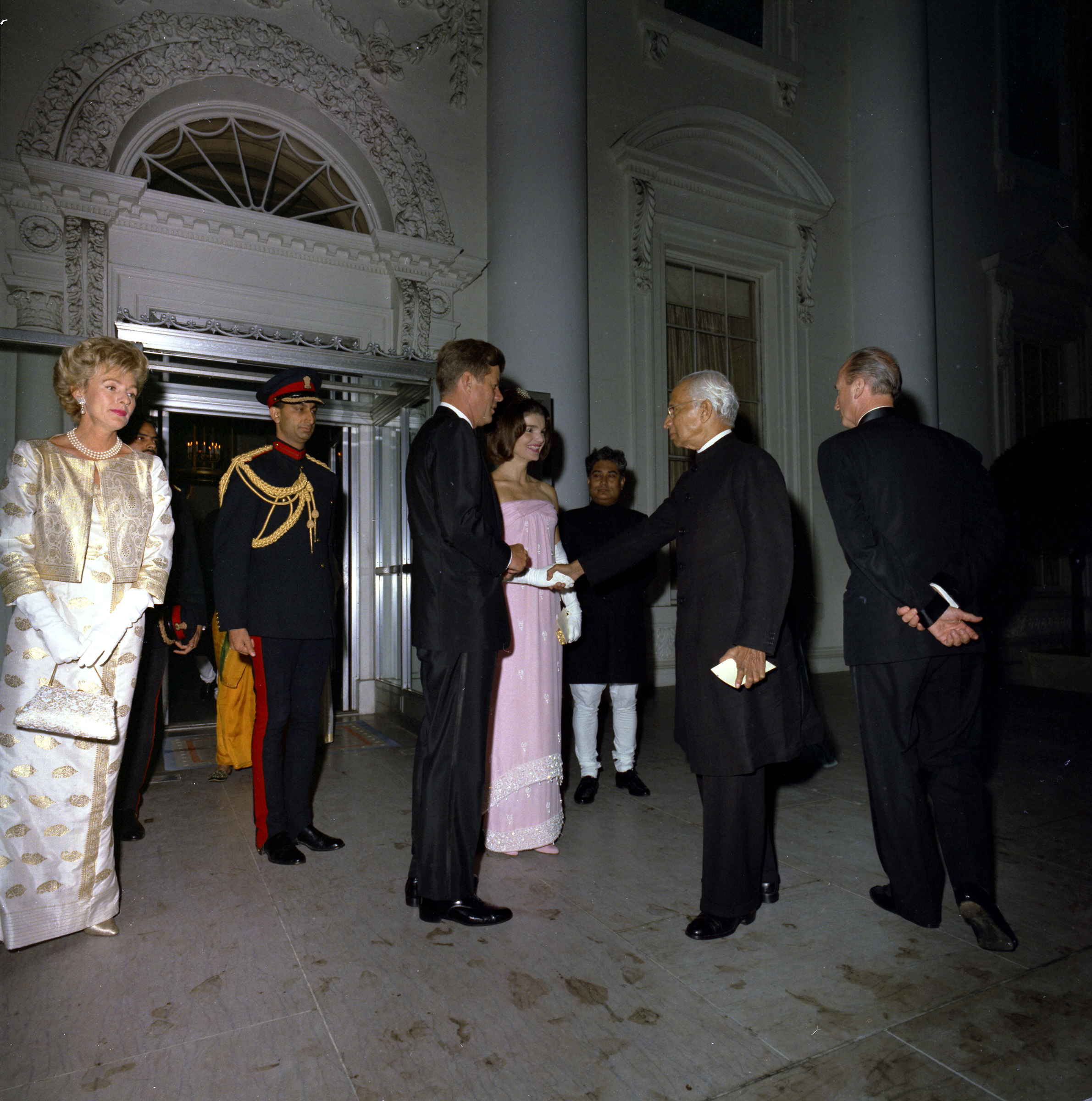 President of India, Dr. Sarvepalli Radhakrishnan, shakes hands with First Lady Jacqueline Kennedy upon his departure from the White House, following a state dinner in his honor; President John F. Kennedy stands at center left. US Chief of Protocol, Angier Biddle Duke, stands at right (back to camera); Robin Chandler Duke (wife of Ambassador Duke) stands at far left. North Portico, White House, Washington, D.C. Robert Knudsen. White House Photographs. John F. Kennedy Presidential Library and Museum, Boston National Archives and Records Administration http://www.jfklibrary.org/Asset-Viewer/Archives/JFKWHP-KN-C28877.aspx