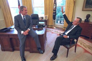 President George W. Bush sits on the edge of his desk Wednesday May 2, 2001, and talks with his father, former President George H.W. Bush who dropped by the Oval Office