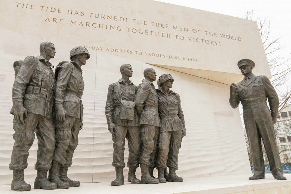 Photograph of the statues and sculptures at the Eisenhower Memorial. The statue depicts Eisenhower speaking to a group of soldiers giving the D-Day address to troops.