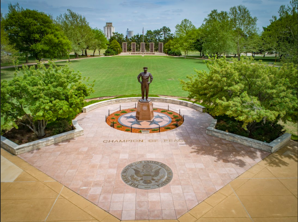 """Photo of the Eisenhower Library Museum campus, showing a statue of Eisenhower in the middle of an emblem with the words """"Champion of Peace."""""""